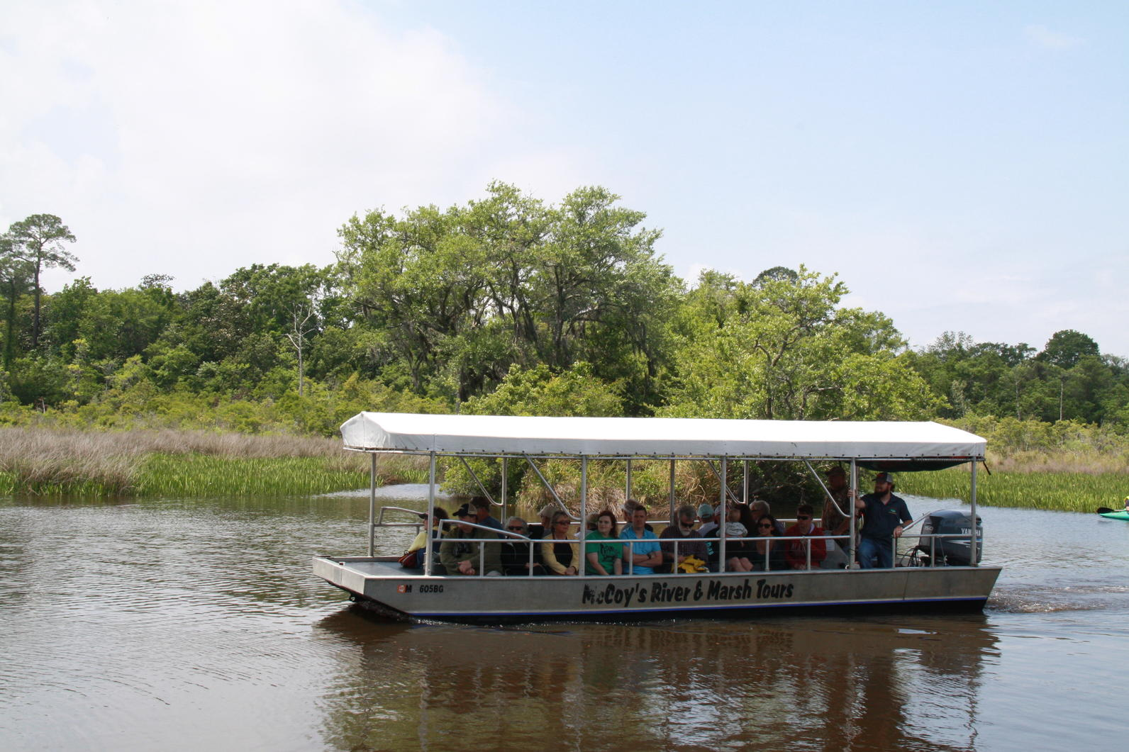 Photo of river with McCoy boat tour full of passengers enjoying nature