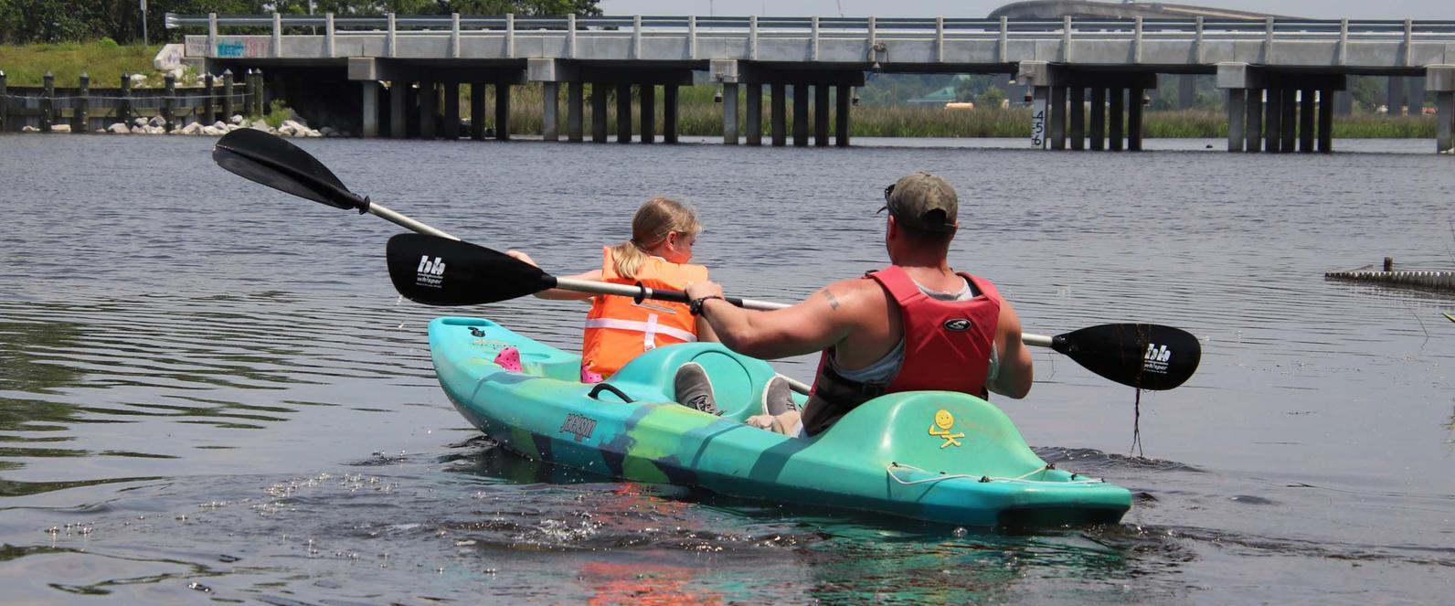 father and daughter kayak the bayou